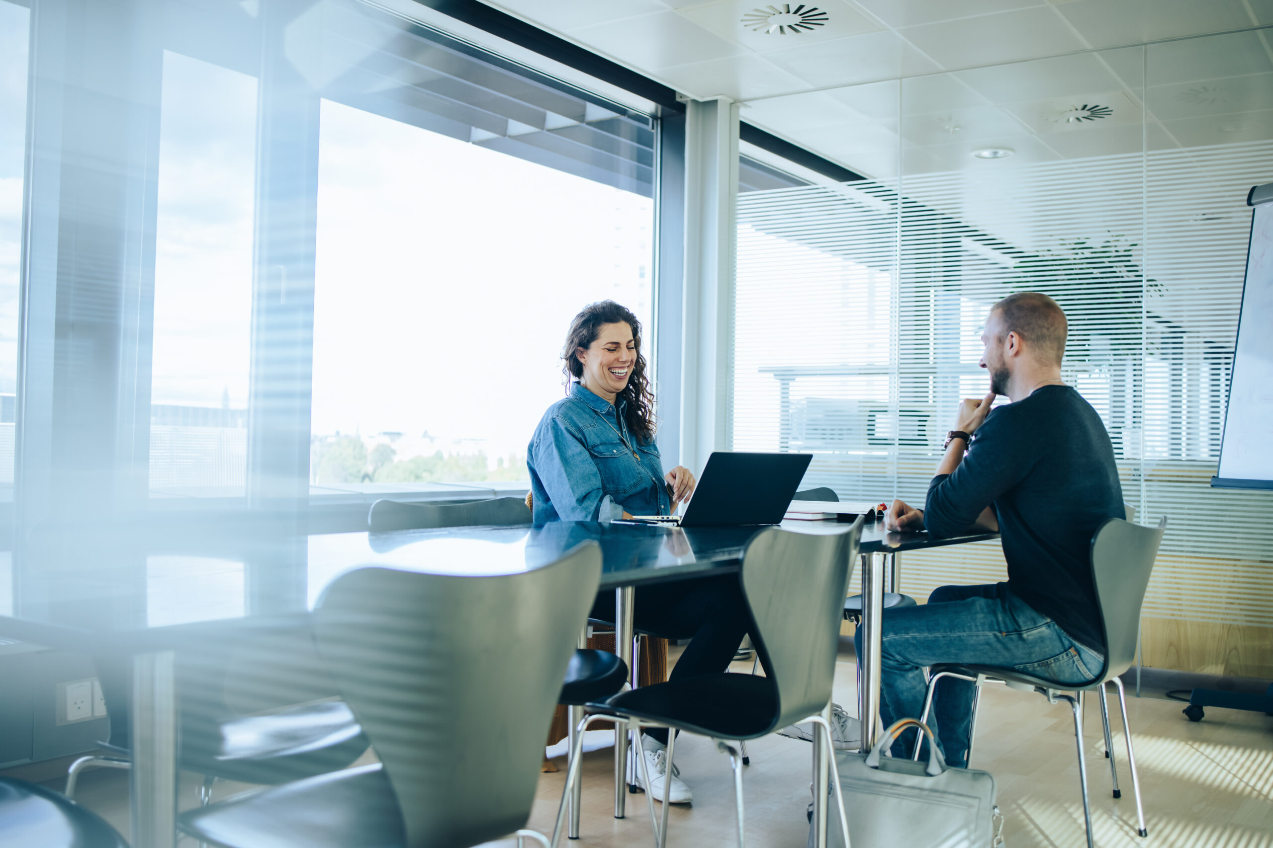 Businesswoman taking interview of a male candidate in office boardroom. Man sitting in a conference room for a job interview.